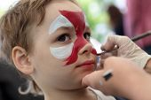 image of face painting  - Person painting boy face at the amusement park  - JPG