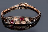 picture of precious stones  - Beautiful golden bracelet with precious stones on grey background - JPG