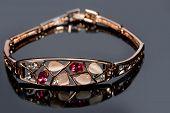 foto of precious stone  - Beautiful golden bracelet with precious stones on grey background - JPG