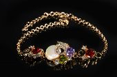 picture of precious stones  - Beautiful golden bracelet with precious stones on black background - JPG