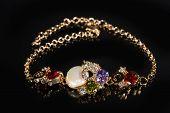 foto of precious stone  - Beautiful golden bracelet with precious stones on black background - JPG