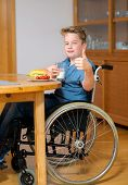 picture of bap  - disabled boy with thumb up in wheelchair is eating in the living room - JPG