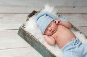 image of sleep  - Newborn baby sleeping in a wooden crate and wearing light blue upcycled pajamas with matching sleeping cap - JPG