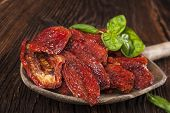 foto of basil leaves  - Sundried tomatoes and fresh basil leaves on brown wooden background - JPG