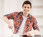 stock photo of hand drill  - Young man using hand drill to build new furniture - JPG