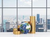 stock photo of golden coin  - Golden coins bar chart and the glove are on the table in a contemporary panoramic office in New York City - JPG