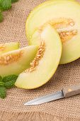 image of muskmelon  - Juicy honeydew melon on a wooden table background - JPG