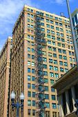 stock photo of stairway  - Older historic highrise with a rustic black stairway on the outside of the building taken in downtown Chicago - JPG