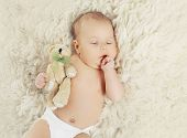 picture of baby bear  - Sweet baby at home sleeping with teddy bear on the fur - JPG