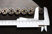 pic of calipers  - Set of few ball bearings and caliper on dark metal background - JPG