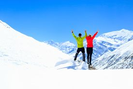 stock photo of winter sport  - Teamwork motivation couple hikers climbers with arms up fitness and sport woman success in winter mountains - JPG