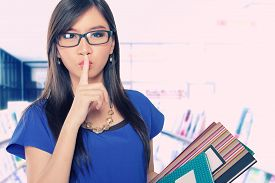 picture of librarian  - Beautiful Asian librarian lady holding some book and asking for silence - JPG
