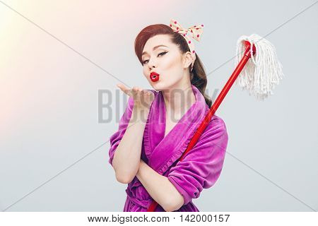 Cute lovely young housewife with mop sending a kiss