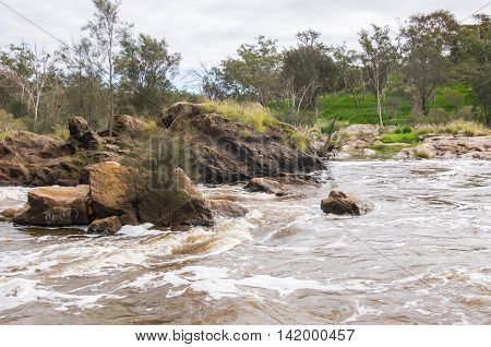 Rocky white waters with lush green landscape at the Bell Rapids under a cloudy sky in the Swan Valley in Western Australia.