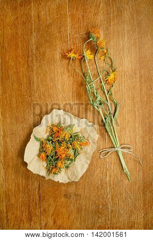 Calendula.Dried herbs for use in alternative medicine.Herbal medicine phytotherapy medicinal herbs.For preparation of infusions decoctions tinctures powders ointments tea.Background wooden board