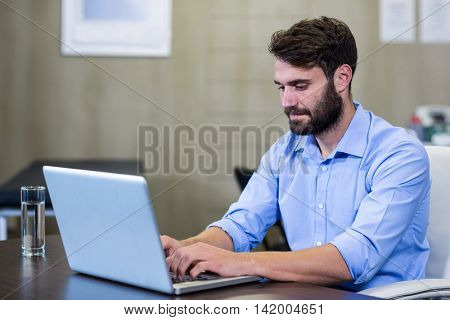 Male therapist using laptop in clinic