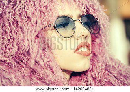 Fashion portrait of stylish pretty woman in sunglasses and purple wig posing in outdoor street fashion