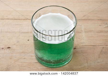 effervescent tablet dissolved in glass of water on wooden table