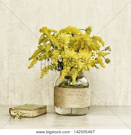 little old book a bouquet of flowers chrysanthemums goldenrod and daisies in a glass vase homemade closeup on gray background closeup. tinted photo