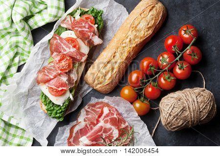 Ciabatta sandwich with romaine salad, prosciutto and mozzarella cheese over stone. Top view