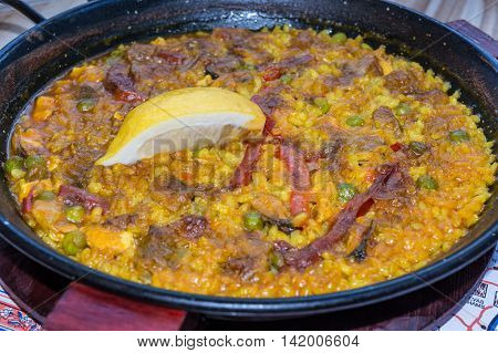 Gourmet Valencia paella with seafood and fresh lobster calamari and mussels with saffron rice and lemon slices closeup.