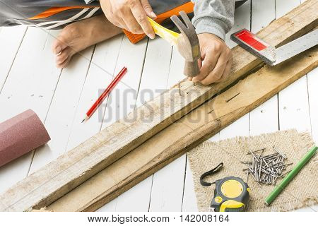 Male carpenter using hammer and nail  at work place.Background craftsman tool.Zoom in01