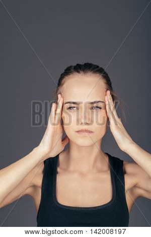 Beautiful woman with migraine and stress puts hands on the head over dark background