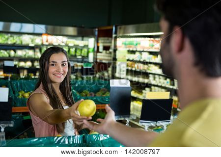Portrait of smiling woman giving fruit to cashier for billing at supermarket