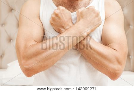Man In White Shirt Holds Fists Near Chest