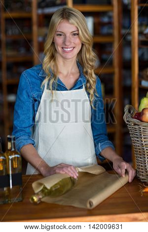Portrait of smiling female staff wrapping olive oil bottle with brown paper in super market