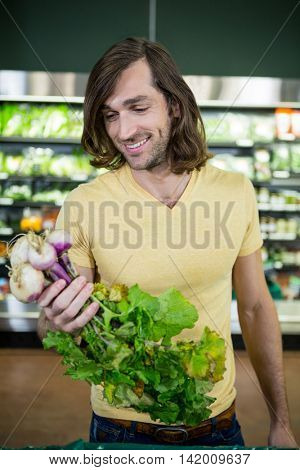 Handsome man holding bunch of fresh turnips in organic section of supermarket
