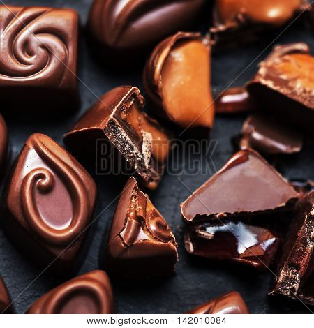 Dark chocolate background - chocolate candies on black table top view. Crushed chocolate pieces with praline