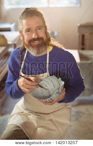 Portrait of smiling male potter painting on bowl in pottery workshop