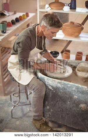 Attentive male potter making pot in pottery workshop
