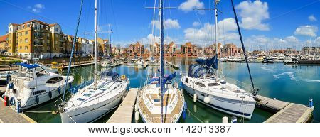 Panoramic view of Sovereign Harbour Marina with moored yachts and modern houses. Eastbourne, East Sussex, England