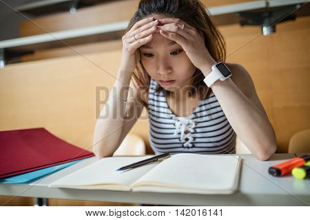 Tensed young woman sitting in classroom at college