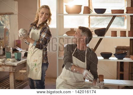 Smiling potters interacting while making pot in pottery workshop