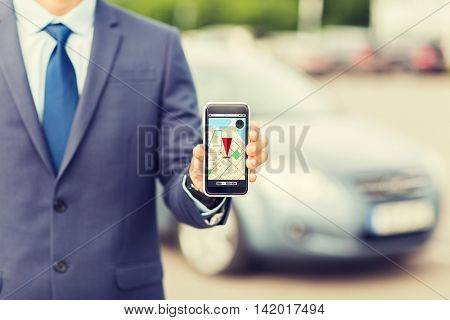 transport, business trip, technology, navigation and people concept - close up of man showing smartphone gps navigator map on screen on car parking