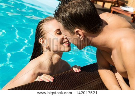 Couple has a rest in the pool with champagne. they are smiling, hugging and kissing