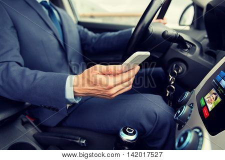 transport, business trip, technology and people concept - close up of young man with smartphone driving car and receiving incoming call from woman on board computer screen