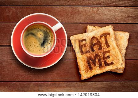 Breakfast, coffee and toast with the text eat me, on a wood background