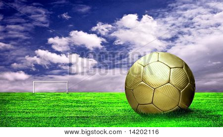 Soccer ball on green grass and sky background