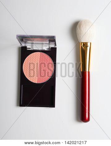 Golden cosmetics - powder blusher brush on light wooden background. flat lay.