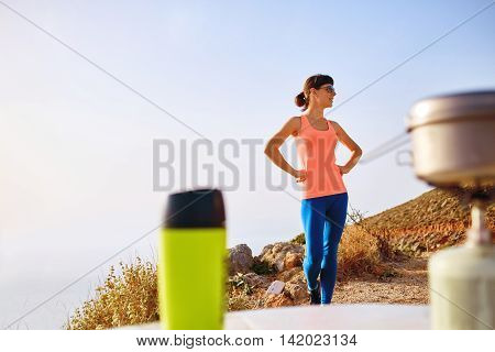 Young sporty looking woman standing in outdoor at the early morning. mugs and burner with a pot in the foreground