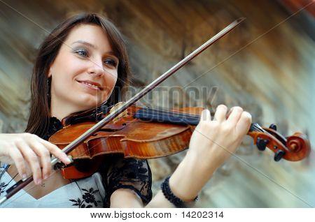 Jugando el violinista sobre el fondo grunge