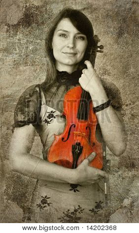 Beautiful female violinist playing violin on the grunge background