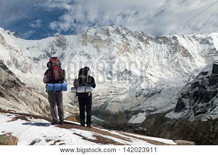 View of Mount Annapurna with two climbers round Annapurna circuit trekking trail Nepal