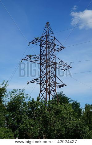Transmission tower with green trees on background of blue sky.