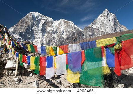 Rows of prayer flags and mounts Arakam Tse Chola Tse and Tabuche peak Sagarmatha national park trek to Everest base camp - Nepal