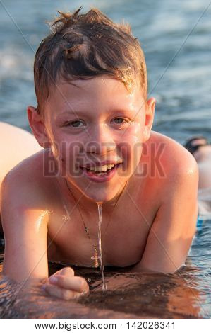Boy lying on the beach in water cheerful and happy